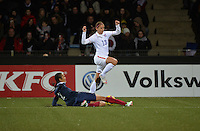Lorient, France. - Sunday, February 8, 2015:  Alex Morgan (13) jumps over a tackle by Wendie Renard (2) of France. France defeated the USWNT 2-0 during an international friendly at the Stade du Moustoir.