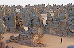 """Except some moufflons  hunters, Touaregs avoid passing in The Tassili of Maghidet natural fortress, nest of """"djenoun"""" or evil geniuses. At dawn, you have to climb on a sandstone peak to discover this amazing rocky labyrinth streching on a pink sand crescent of 45 km long."""