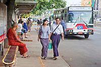 Myanmar, Burma.  Yangon, Bus Stop on Sule Pagoda Road.  The man and woman are wearing a longyi, the Burmese sarong.