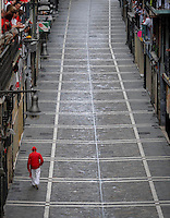 A man walks along Estafeta street before the fifth San Fermin Festival bull run, on July 11, 2012, in Pamplona, northern Spain. The festival is a symbol of Spanish culture that attracts thousands of tourists to watch the bull runs despite heavy condemnation from animal rights groups. (c) Pedro ARMESTRE