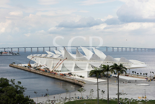 Workers put the final touches to the Museu do Amanhã (Museum of Tomorrow) working from a line of cherry pickers with the Niteroi Bridge behind. Praça Mauá, Rio de Janeiro, Brazil.