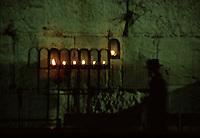 ISRAELE, Gerusalemme: il Muro del pianto di notte. Un ebreo e delle candele accese davanti al muro.
