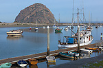 San Luis Obispo County, CA<br /> Boats and dinghies docked in the harbor at Morro Bay with Morro rock in the distance