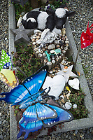 Switzerland. Canton Bern. Sankt Stephan (St. Stephan). Graveyard near the protestant  church. Tomb of a deceased child. Toys and sculptures. A butterfly, a stone with a heart shape and written german words (wir vermiessen dich - we miss you), a plastic tractor, an angel, two stars, a veal's puppet and a paper windmill with swiss flags. St. Stephan is a municipality in the Obersimmental-Saanen administrative district. 2.11.2020 © 2020 Didier Ruef