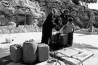 Palestinian woman fill containers of water at a local well in the Palestinian village of Twani, in the West Bank. The water crisis has increased in the West Bank in the last months due the Israeli restrictions on water. Amnesty International has accused Israel of denying Palestinians adequate access to water while allowing Jewish settlers in the occupied West Bank almost unlimited supplies. Photo by Quique Kierszenbaum