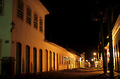 Paraty, Brazil. Colonial buildings in the village at night with artificial street lighting and a bicycle.