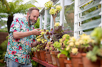 BNPS.co.uk (01202) 558833. <br /> Pic: CorinMesser/BNPS<br /> <br /> Pictured: Mike Clifford tends to the plants in his exotic garden. <br /> <br /> A gardener who spent years cultivating some of the world's rarest plants is opening his exotic bungalow garden for charity. <br /> <br /> Mobile home designer, Mike Clifford, began tropical gardening over 20 years ago when he was inspired by a documentary on the subject.  <br /> <br /> Since then, he and his wife Tina, who makes cakes for visitors, have cultivated thousands of plants from across the globe in their quaint English garden.