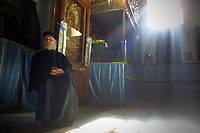 Greek-Orthodox priest Father Neofitis, 82, enjoys the warmth of sunbeams streaming in the Church of the Nativity December 20, 2001.