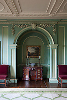An arched alcove in the living room houses an antique desk, ornately carved with a neo- classical, geometric design. Stucco swags adorn the wall above