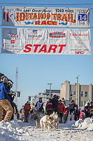 Mike Ellis and team leave the ceremonial start line at 4th Avenue and D street in downtown Anchorage during the 2014 Iditarod race.<br /> Photo by Jim R. Kohl/IditarodPhotos.com