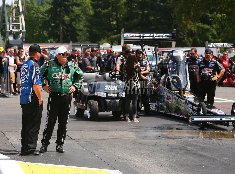 Aug. 2, 2014; Kent, WA, USA; NHRA funny car driver John Force talks to Robert Hight as he stands alongside the top fuel dragster of daughter Brittany Force and team during qualifying for the Northwest Nationals at Pacific Raceways. Mandatory Credit: Mark J. Rebilas-