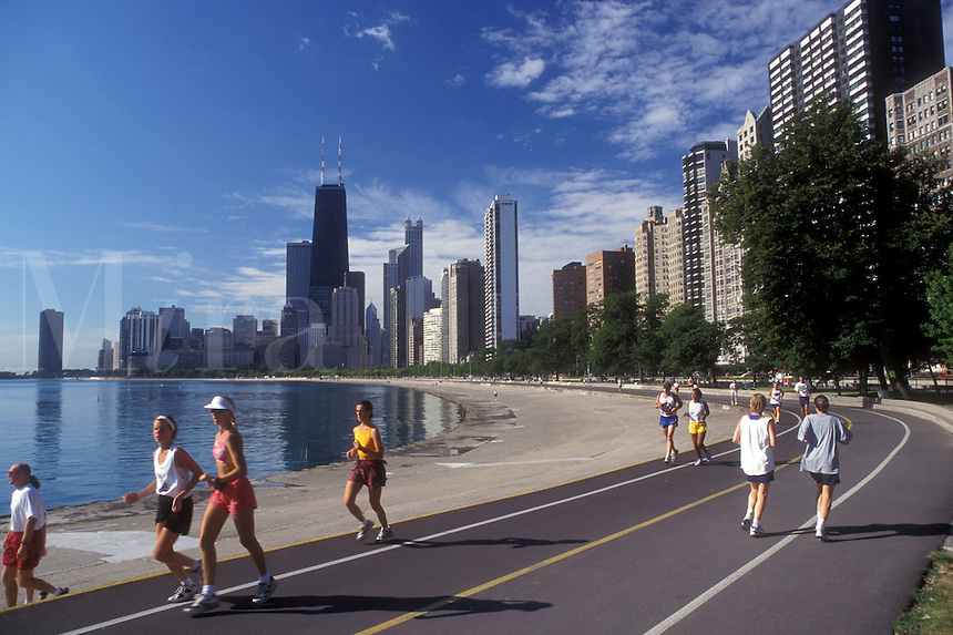 Chicago, Illinois, People jog on the recreation path on the waterfront of Lake Michigan. The skyline of downtown Chicago towers.