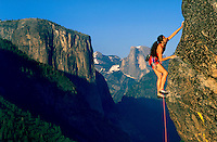 Woman climbing a rocky outcropping in Yosemite Valley, California with mountains and blue sky in the background.<br />