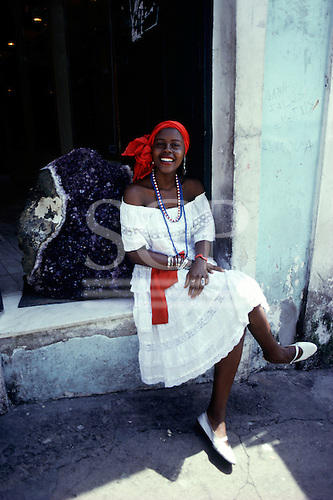 Salvador, Bahia State, Brazil. Smiling girl in a red headscarf sitting in front of a large amethyst.