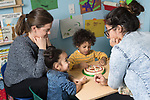 Education Preschool classroom scenes 2-3 year olds boy and girl working with speech therapist, therapy intern looking on