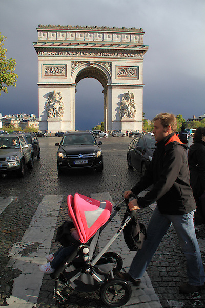 Father with baby stroller and Arc de Triomphe, along the Avenue des Champs Elysees, Paris, France. .  John offers private photo tours in Denver, Boulder and throughout Colorado, USA.  Year-round. .  John offers private photo tours in Denver, Boulder and throughout Colorado. Year-round.