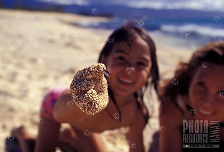 Girl holding up a tiny fish while mother looks on at beach on North Shore of Oahu
