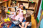 Education preschool 3-4 year olds group of three  girls playing together with dolls in strollers and puppets