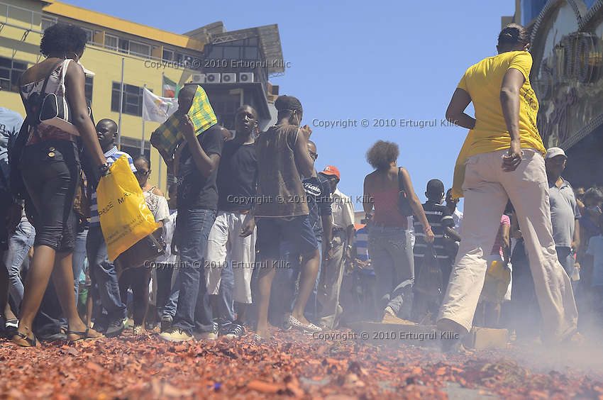 Visitors are walking on billions of small red cartons, rest of hundred meters long firecrackers while the smoke still on the them because the final explosion done just less then a minute a go.....End of year 2010 celebrations on the streets of Paramaribo. Suriname is one of biggest consumer in South America that using firecrackers, fireworks ( also locally known as pagara ) for celebrations, especially for end of every years and also beginning of every new Chinese Years.
