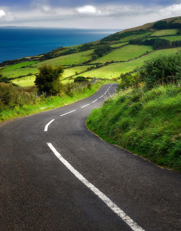 Road near Torr Head with green fields in background. Antrim Coast Northern Ireland
