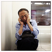A man talks on his cellphone on the subway in Beijing.