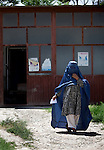 5 June 2013, Kholm District Hospital, Mazar-i-Sharif, Balkh Province, Afghanistan.  Patients come and go  to see Dr Maliha Aziz , Chief Medical Officer at the Kholm District Hospital outside Mazar-i-Sharif.The hospital which has 54 beds and before 2004 was only a clinic is funded by the Strengthening Health Activities for Rural Poor Project (SHARP). SHARP aims to improve the health and nutrition status of Afghans, focusing especially on women and children and the underserved areas of the country. Already remarkable progress has been made in the reduction of infant and under five mortality as well as pregnancy related mortality. With World Bank support in 11 provinces the number of health clinics has nearly tripled from 148 to 432 and about 85% of the population now lives in districts which now have service providers to deliver a basic package of health service.  The project supports Afghanistan's Health and Nutrition Sector Strategy  which is the governments blueprint for the health sector program for the period 2008-13. Picture by Graham Crouch/World Bank.
