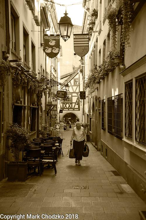 Old woman walks down small street.
