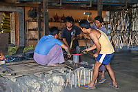 Myanmar, Burma.  Three Young Men Hammer Red-hot Metal Just Taken from the Blacksmith's Fire, Inle Lake, Shan State.