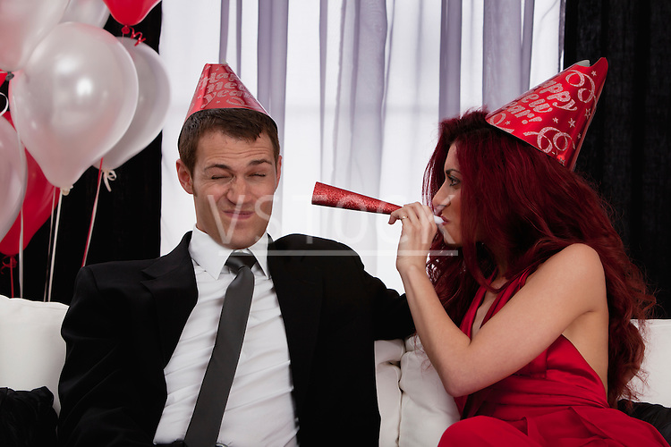 Couple celebrating birthday by playing with paper blow horns