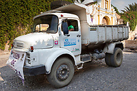 Antigua, Guatemala. A municipal street-cleaning truck follows a procession in order to clean up the remnants of an alfombra (carpet) of flowers, pine needles, and other traditional materials immediately after  the passage of a procession during Holy Week, La Semana Santa.  This Brazilian-made truck is a gift of Switzerland, and is powered with biodiesel fuel.