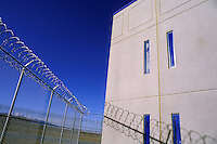 New prison construction in the Western United States, exterior view of fence and housing unit. Western United States.