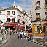 Montmartre, Paris.  Rue Norvins leading to the Place du Tertre where artists sketch patrons.  One can see the Sacre Coeur in the background.  This neighborhood on top of the hill maintains its small, cobblestone streets -- Rue Norvins, St Rustique, among others.