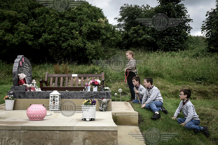 Irish Traveller Viviana and her triplet brothers Richard, John Button and David look at at the grave of a young woman.