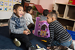 Education Preschool 3-4 year olds boys and girls playing with doll house and plastic castle in classroom