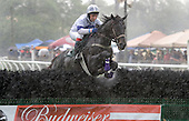 Primero Peru and Roddy Mackenzie splash through the final jump in the James Maloney maiden hurdle, during the height of an intense storm that ripped through Aiken.