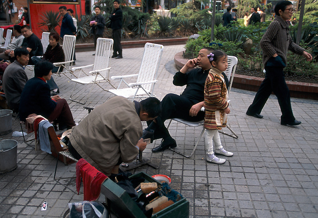 Morning shoe shine in city park; father on cell phone; daughter near; business; Wuxi, China, Asia; 042503
