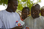 A Society for Family Health (SFH)-trained HIV/AIDS prevention volunteer talks to men in Yankaba market in Kano, Nigeria, about HIV counseling and testing services, showing them a referral card that lists counseling and testing sites.  The   Society for Family Health (SFH) is Nigeria's largest indigenous non-profit and affiliate of the international social marketing organization, Population Services International (PSI).