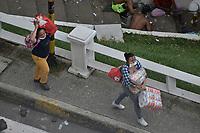 CALI - COLOMBIA, 28-04-2021: Un par de mujeres llevan el prodcuto del saqueo de un supermercado en el oeste de la ciudad de Cali durante la jornada del Paro nacional en Colombia hoy, 28 abril de 2021, para protestar por la reforma tributaria que adelanta el gobierno de Ivan Duque además de la precaria situación social y económica que vive Colombia. El paro fue convocado por sindicatos, organizaciones sociales, estudiantes y la oposición. / Two women carry the prodcut of the looting of a supermarket in the west of the city of Cali during the day of the national strike in Colombia today, April 28, 2021, to protest the tax reform carried out by the government of Ivan Duque in addition to the precarious social and economic situation that Colombia is experiencing. The strike was called by unions, social organizations, students and the opposition in Colombia. Photo: VizzorImage / Gabriel Aponte / Staff