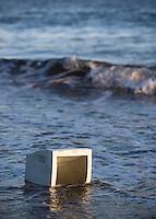 Disgarded obsolete broken computer monitor left abandon on public beach
