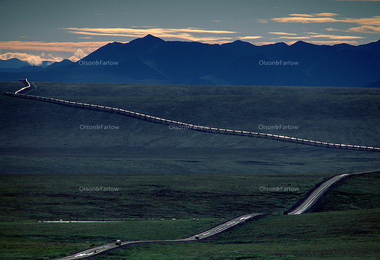 """Thin ribbon of humanity flows north across the tundra along Alaska's Dalton Highway; nearby, the trans-Alaska pipeline carries Prudhoe Bay oil south 800 miles to the port of Valdez.  The road, built for the pipeline, is known as the """"haul road"""" for the trucks carrying supplies as the pipeline was built.  The Alaska pipeline runs through BLM land above the Yukon River and Brooks Range, and originally cost $8 billion in 1977."""