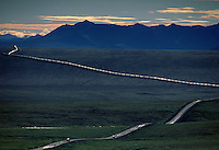 "Thin ribbon of humanity flows north across the tundra along Alaska's Dalton Highway; nearby, the trans-Alaska pipeline carries Prudhoe Bay oil south 800 miles to the port of Valdez.  The road, built for the pipeline, is known as the ""haul road"" for the trucks carrying supplies as the pipeline was built.  The Alaska pipeline runs through BLM land above the Yukon River and Brooks Range, and originally cost $8 billion in 1977."