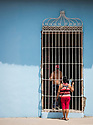 27/07/18<br /> <br /> A woman with fan talks to a man through bars on window-less house. Trinidad, Cuba.<br /> <br /> All Rights Reserved, F Stop Press Ltd. (0)1335 344240 +44 (0)7765 242650  www.fstoppress.com rod@fstoppress.com