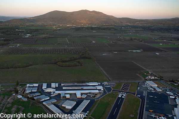 aerial photograph of Lampson Field airport (1O2), Lakeport, Lake County, California toward Mount Konocti at dusk, a Piper Malibu waits for take off in the run up area.