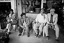 Turquie 1997.Un gardien de village devant une épicerie à Midiat..Turkey 1997.In Midiat, men in the street in front a shop with a militiaman