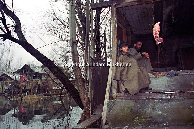 A butcher and his son at their beef shop in Dal Lake, Srinagar, Kashmir valley, India.