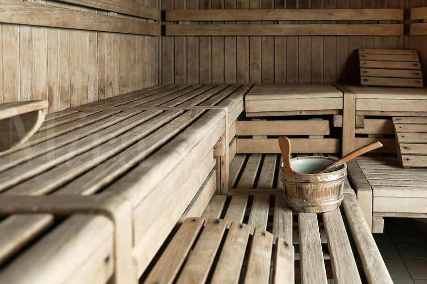 Spa wooden sauna interior with water bucket.