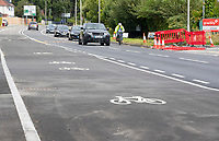 BNPS.co.uk (01202) 558833. <br /> Pic: CorinMesser/BNPS<br /> <br /> Pictured: A car veers into the opposite lane to overtake a cyclist still using the regular carriageway and not the brand new cycle lane.<br /> <br /> A cycle lane which is believed to be one of Britain's widest has been slammed by road users who are bemused by its size.<br /> <br /> Despite measuring over half as wide as the adjacent road, cyclists have still been spotted using the carriageway instead of the cycle lane.<br /> <br /> The cycle way is a whopping 11ft wide, 2ft wider than the vehicle lane which locals say is frequented by heavy goods and emergency vehicles.<br /> <br /> Residents on Wimborne Road West in Wimborne, Dorset, were exasperated when they woke one morning to the 'cycle highway' as it has been dubbed by the local council.<br /> <br /> It is part of a major £102 million scheme to make travel more sustainable and reduce congestion across the county but they argue it could have the opposite effect by obstructing traffic.