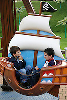 Italy. Province of Veneto. Castelnuovo del Garda. Nicola Ruef and a boy at the attraction: Baby Corsaro. A rolling wheel with two seats on small pirates boats. A black flag with a death head. Gardaland is the biggest amusement park in Italy and one of the largest in the whole of Europe. © 2006 Didier Ruef
