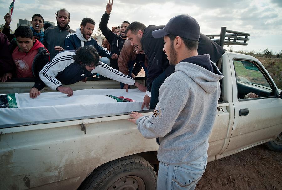 Men shout anti-Gaddafi slogans above casket at a funeral in Benghazi, Libya.
