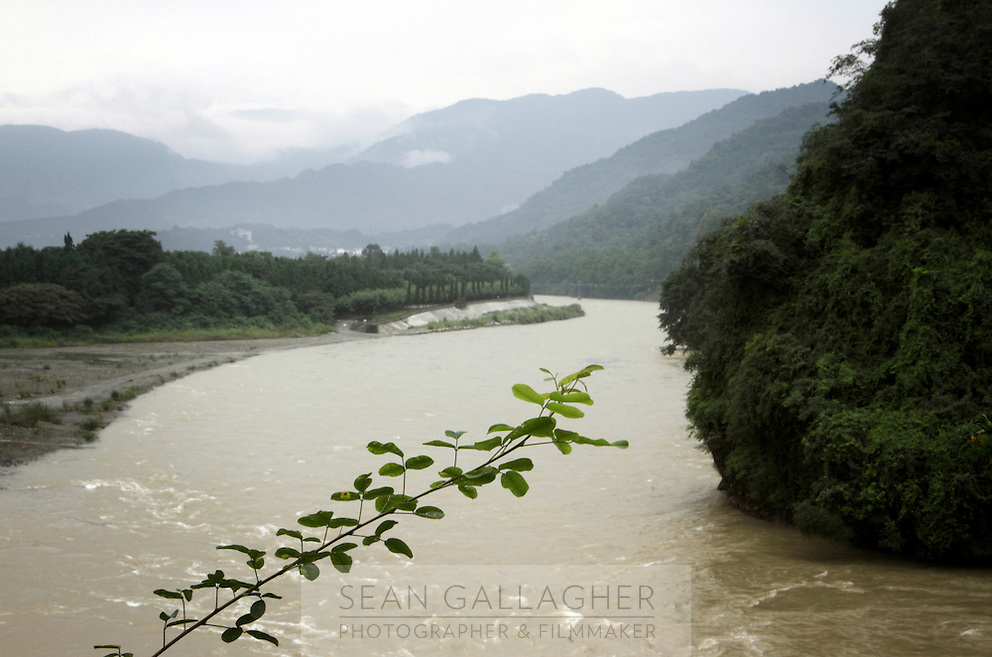 """A view of the the Dujiangyan Irrigation System and surrounding mountains. The system is regarded as an """"ancient Chinese engineering marvel."""" By naturally channeling water from the Min River during times of flood, the irrigation system served to protect the local area from flooding and provide water to the Chengdu basin. Sichuan Province. 2010"""